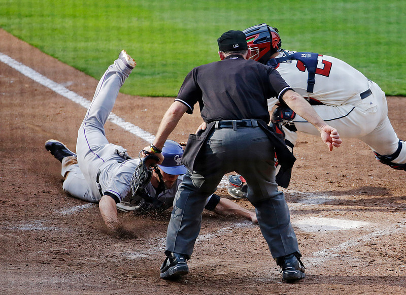. Colorado Rockies\' Charlie Culberson, left, beats the tag from Atlanta Braves catcher Evan Gattis, right, to score off a fielder\'s choice by teammate Charlie Blackmon in the seventh inning of a baseball game, Saturday, May 24, 2014, in Atlanta. (AP Photo/David Goldman)