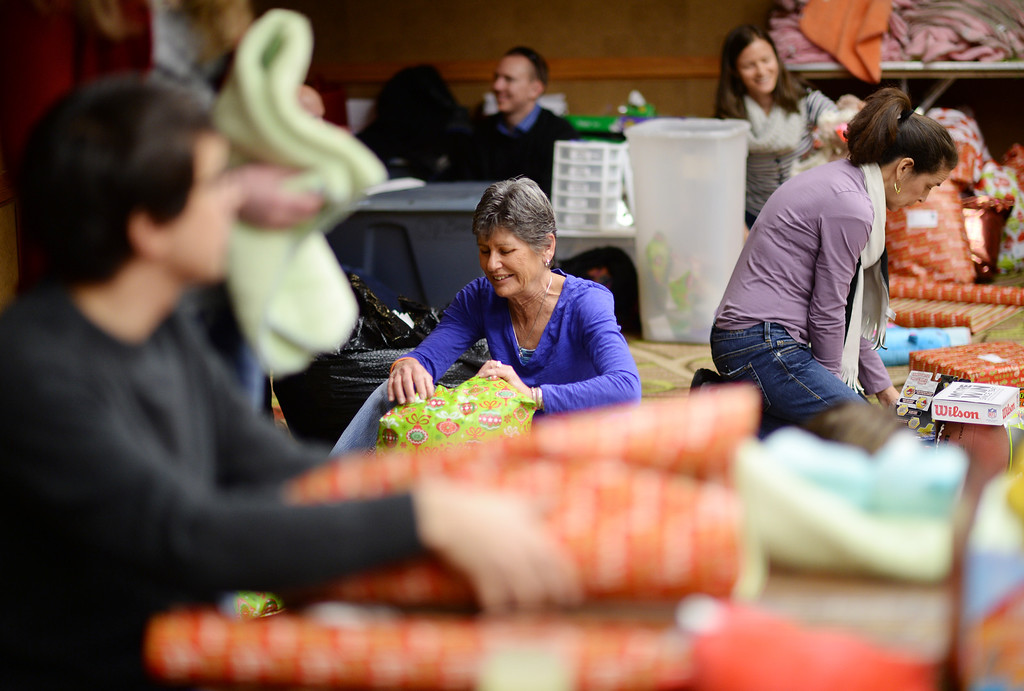 ". DENVER, CO. DECEMBER 21: Chris Lawson of Denver, front center, is wrapping Christmas gift during the annual Father Woody Christmas Party in Denver, Colorado December 21, 2013. In advance of handing out 5,000 gifts, volunteers are doing a ""wrapping party\"" at the Sheraton Denver Downtown Hotel. (Photo by Hyoung Chang/The Denver Post)"