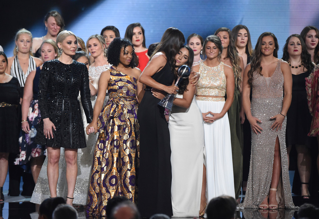 . Jennifer Garner, front, embraces gymnast Aly Raisman after presenting the Arthur Ashe Award for Courage, at the ESPY Awards at Microsoft Theater on Wednesday, July 18, 2018, in Los Angeles. Holding hands in front left are former gymnast Sarah Klein and former Michigan State softball player Tiffany Thomas Lopez. More than 140 survivors of sexual abuse by a former team doctor for USA Gymnastics and Michigan State University joined hands on stage to be honored with the award. (Photo by Phil McCarten/Invision/AP)