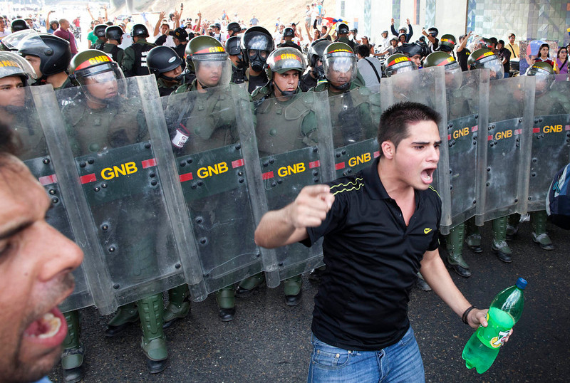 . Opposition supporters confront riot police as they block on a highway in the Altamira neighborhood of Caracas, Venezuela, Monday, April 15, 2013. National Guard troops dispersed students protesting the official results of Venezuela\'s disputed presidential election. Opposition candidate Henrique Capriles has challenged his narrow loss to Nicolas Maduro and is demanding a recount. (AP Photo/Ramon Espinosa)