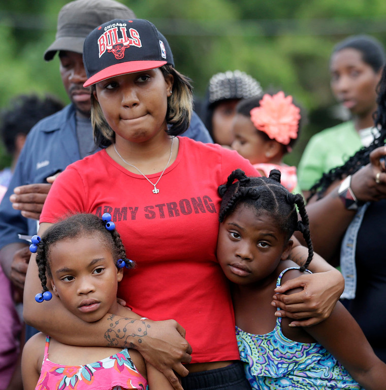 . Raven Williams, center, holds her cousins Dynecia LeBouf, 8, left, and Dyjaye LeBouf, 9, right, at a vigil for missing 6-year-old Ahlittia North, at the location where her body was found in a trash bin, just doors down from where she disappeared, in Harvey, La., Tuesday, July 16, 2013. Ahlittia disappeared from her apartment late Friday night or early Saturday morning.  (AP Photo/Gerald Herbert)