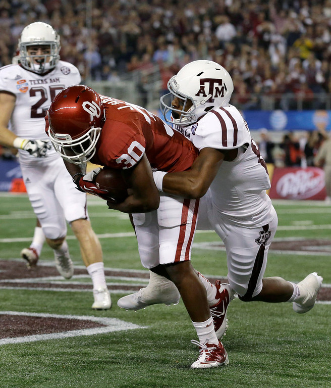 . Oklahoma \'s Javon Harris (30) intercepts a pass in the end zone intended for Texas A&M\'s Malcome Kennedy, right, in the first half of the Cotton Bowl NCAA college football game Friday, Jan. 4, 2013, in Arlington, Texas. A&M\'s Ryan Swope is at left rear. (AP Photo/LM Otero)