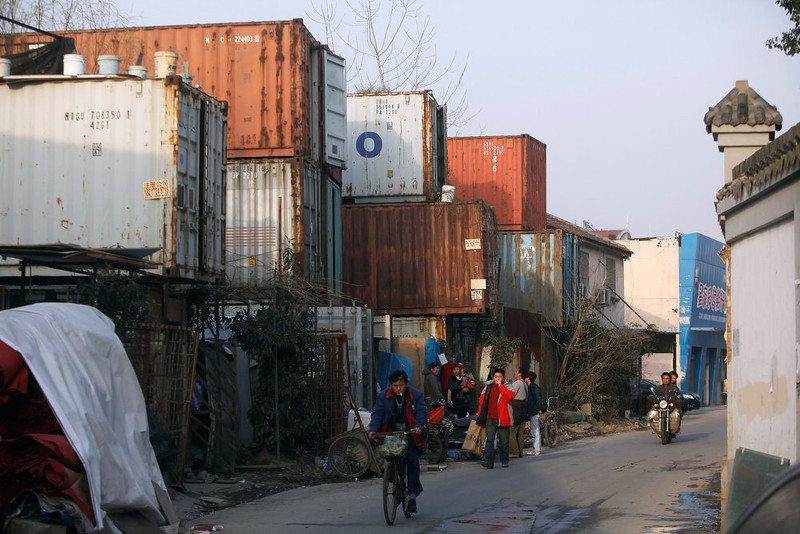 . People stand outside shipping containers serving as their accommodation, in Shanghai March 4, 2013. The containers, which house different families, were set up by the landlord, who charges a rent of 500 yuan ($ 80) per month for each container. REUTERS/Aly Song