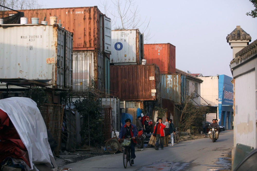 Description of . People stand outside shipping containers serving as their accommodation, in Shanghai March 4, 2013. The containers, which house different families, were set up by the landlord, who charges a rent of 500 yuan ($ 80) per month for each container. REUTERS/Aly Song