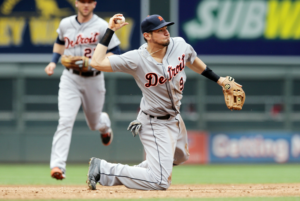 . Detroit Tigers third baseman Nick Castellanos throws to first as shortstop Andrew Romine, left, backs him up, but Minnesota Twins\' Eduardo Nunez beat the throw for a single  in the second inning of a baseball game, Saturday,  Aug. 23, 2014, in Minneapolis. (AP Photo/Jim Mone)