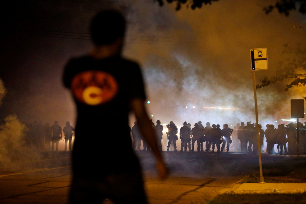 . A man watches as police walk through a cloud of smoke during a clash with protesters Wednesday, Aug. 13, 2014, in Ferguson, Mo. (AP Photo/Jeff Roberson)