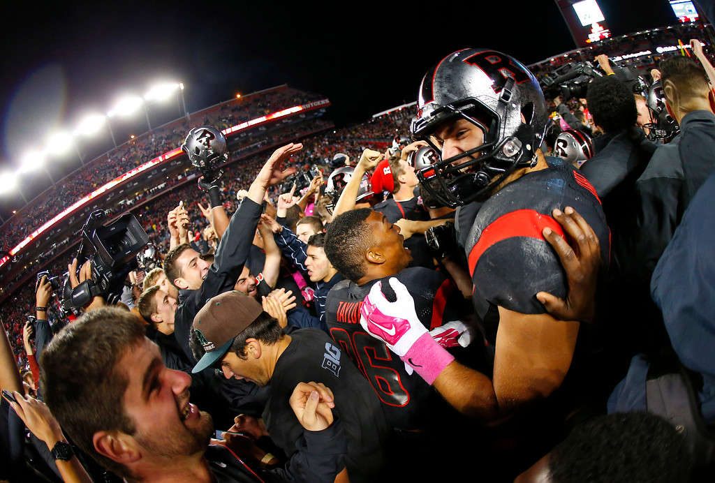 . Rutgers\' Charles Scarff celebrates as fans flood the field after Rutgers defeated Michigan 26-24 in an NCAA college football game Saturday, Oct. 4, 2014, in Piscataway, N.J. (AP Photo/Rich Schultz)