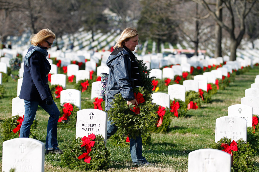 . Volunteers Denise Burke, right, and Heidi Johnson help to place holiday wreaths over the graves of fallen soldiers during Wreaths Across America Day at Arlington Cemetery on Saturday Dec. 10, 2011. (AP Photo/Jose Luis Magana)