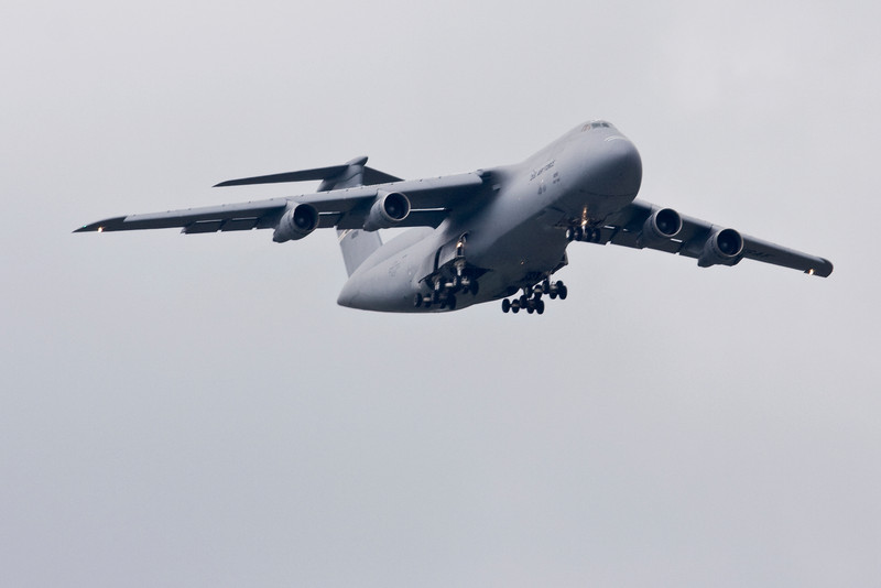 The C-5 Galaxy is one of the largest aircraft in the world with a wingspan of over 220 feet and a height of 65 feet.  It can carry a payload of 270,000 lbs around the world with aerial refueling.