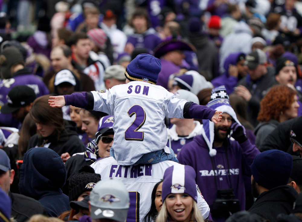 . A man and his son, fans of Super Bowl XLVII champion Baltimore Ravens, celebrate their victory before a stadium rally in Baltimore February 5, 2013. The Ravens defeated the San Francisco 49ers to win the NFL championship.     REUTERS/Gary Cameron