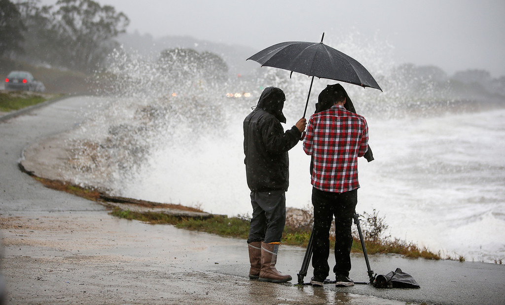 . People take photos of waves crashing along coast in El Granada, Calif., on Thursday, Dec. 11, 2014. (John Green/ Bay Area News Group)