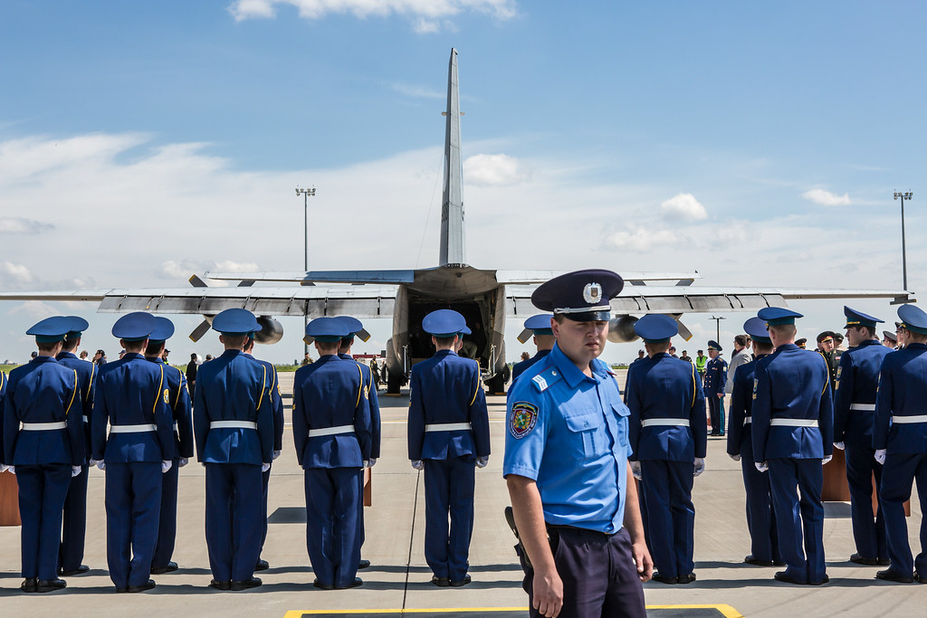 . Members of the Ukrainian military stand to attention after coffins containing the bodies of victims of the crash of Malaysia Airlines flight MH17 were loaded onto a plane for transport to the Netherlands during a departure ceremony on July 23, 2014 in Kharkiv, Ukraine. Malaysia Airlines flight MH17 was travelling from Amsterdam to Kuala Lumpur when it crashed killing all 298 on board including 80 children. The aircraft was allegedly shot down by a missile and investigations continue over the perpetrators of the attack. (Photo by Brendan Hoffman/Getty Images)