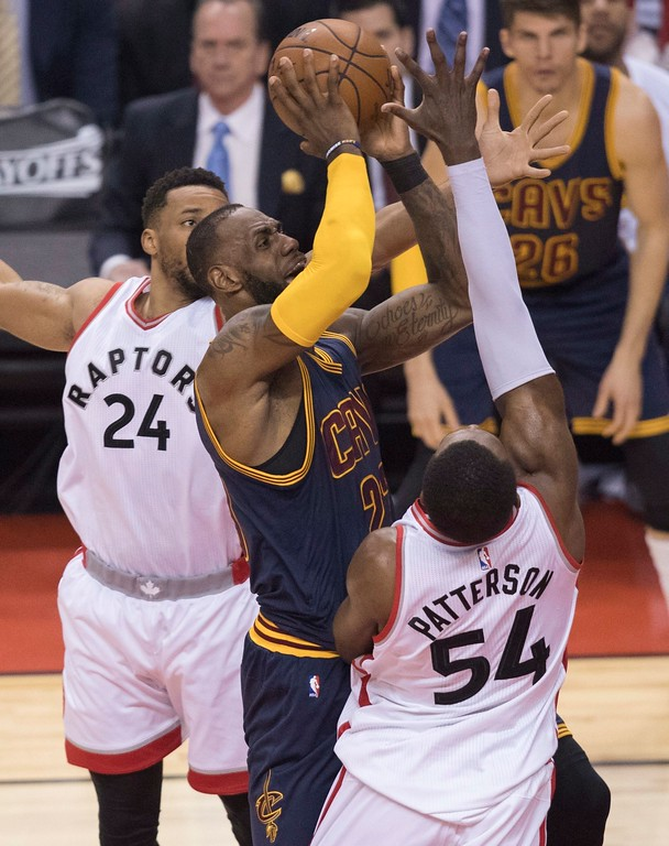 . Cleveland Cavaliers\' LeBron James, center, drives to the basket between Toronto Raptors\' Norman Powell, left, and  Patrick Patterson during the first half of Game 3 of an NBA basketball second-round playoff series in Toronto on Friday, May 5, 2017. (Fred Thornhill/The Canadian Press via AP)