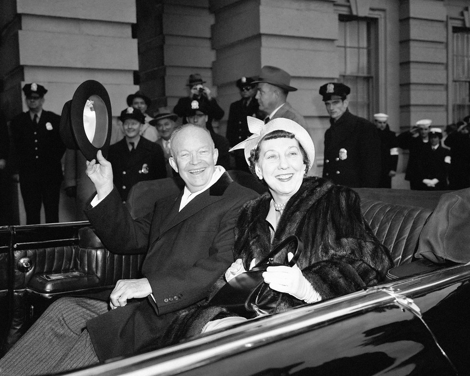 . President Dwight Eisenhower and Mrs Mamie Eisenhower sit  in the open car and wave as they  leave the Capitol in Washington Jan. 21, 1957, just before swinging into Constitution Avenue on traditional inaugural parade route. (AP Photo)