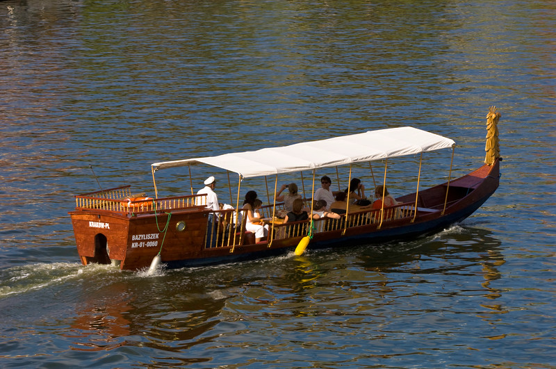 Poland, Cracow, tourists in a boat on Vistula River by Wawel Hill