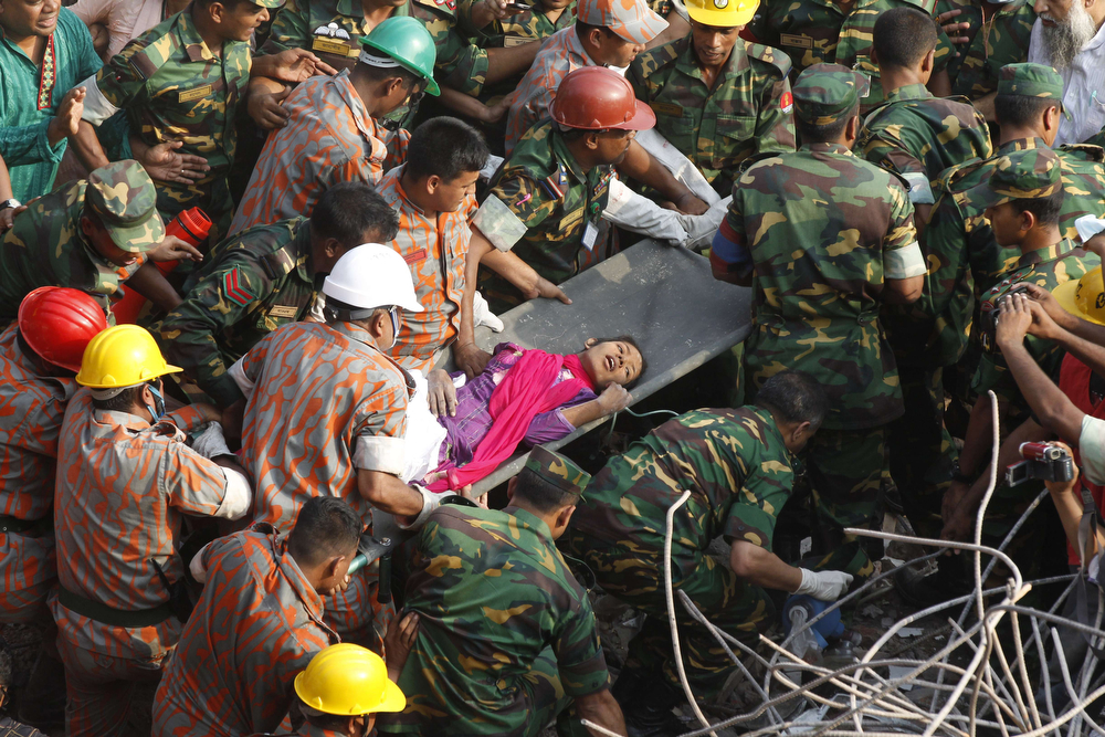 """. In this photograph taken on May 10, 2013, Bangladeshi rescuers retrieve garment worker Reshma from the rubble of a collapsed building in Savar on the outskirts of Dhaka seventeen days after the eight-storey building collapsed. Reshma Akhter, 19, was a rare bright spot in the Rana Plaza catastrophe on the outskirts of the Bangladeshi capital Dhaka on April 24, 2013, that left 1,138 dead and more than 2,000 injured. She was the \""""miracle\"""" seamstress, plucked from the rubble of the world\'s worst garment factory disaster 17 days after her factory collapsed. One year on, she has married and found a new job. (AFP/Getty Images)"""