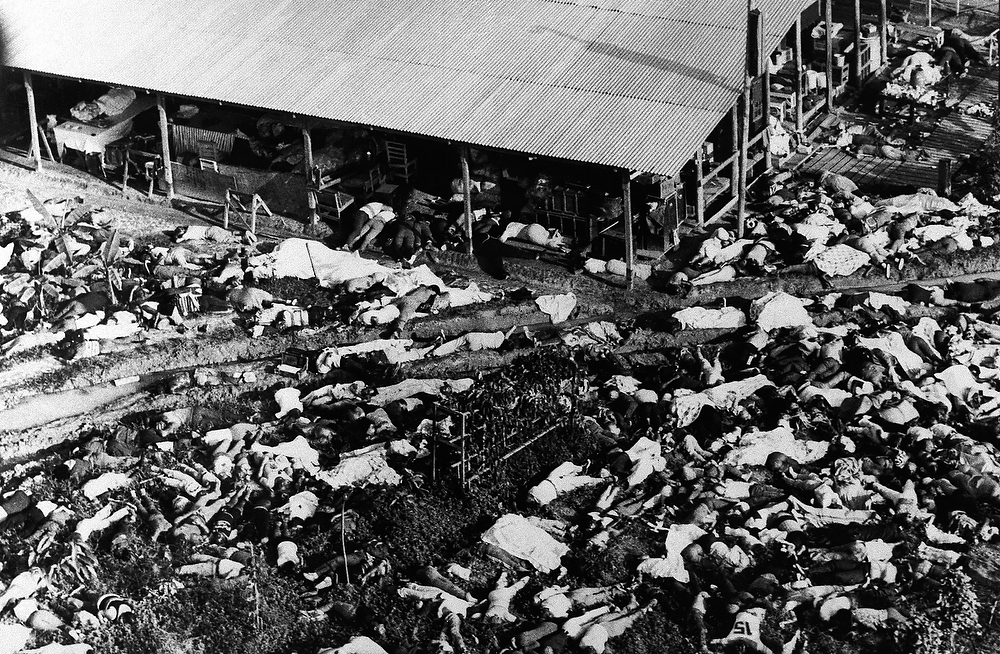 Description of . Bodies lie about a building at the People's Temple Commune in Jonestown, Guyana, on November 17, 1978 in a mass suicide that resulted in more than 900 deaths after leader Jim Jones claimed they would be transported to another planet where they would live in peace in a new eden avoiding a nuclear fire that would engulf the earth. (AP Photo/Frank Johns)