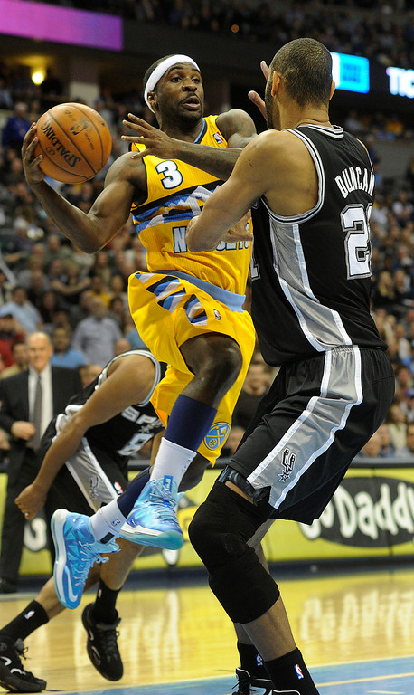 . Denver guard Ty Lawson (3) looked to pass around Spurs forward Tim Duncan (21) in the second half. The Denver Nuggets defeated the San Antonio Spurs 112-106 at the Pepsi Center Tuesday night, December 18, 2012. Karl Gehring/The Denver Post