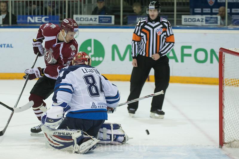 Andris Dzerins (25) of Dinamo Riga play in front of the goalkeeper of Neftekhimik Nizhnekamsk Ivan Lisutin (84)