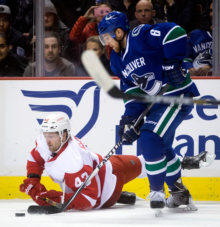 . Detroit Red Wings\' Darren Helm, left, falls to the ice while battling for the puck with Vancouver Canucks\' Yannick Weber, of Switzerland, during the first period of an NHL hockey game in Vancouver, British Columbia on Saturday, Jan. 3, 2015. (AP Photo/The Canadian Press, Darryl Dyck)