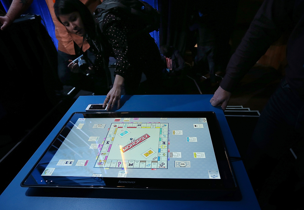 . A reporter compares the size of a cell phone to the new Lenovo IdeaCentre Horizon Table PC during an Intel press conference at the 2013 International CES at the Mandalay Bay Convention Center on January 7, 2013 in Las Vegas, Nevada. (Photo by Justin Sullivan/Getty Images)