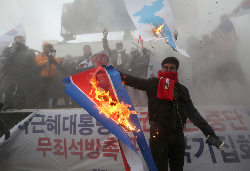 ". A protester burns a North Korean flag during a rally against North Korea\'s participation in the 2018 Pyeongchang Winter Olympics in Seoul, South Korea, Sunday, Feb. 11, 2018. A rare invitation to Pyongyang for South Korean President Moon Jae-in marked Day Two of the North Korean Kim dynasty\'s southern road tour, part of an accelerating diplomatic thaw that included some Korean liquor over lunch and the shared joy of watching a ""unified\"" Korea team play hockey at the Olympics. (AP Photo/Ahn Young-joon)"