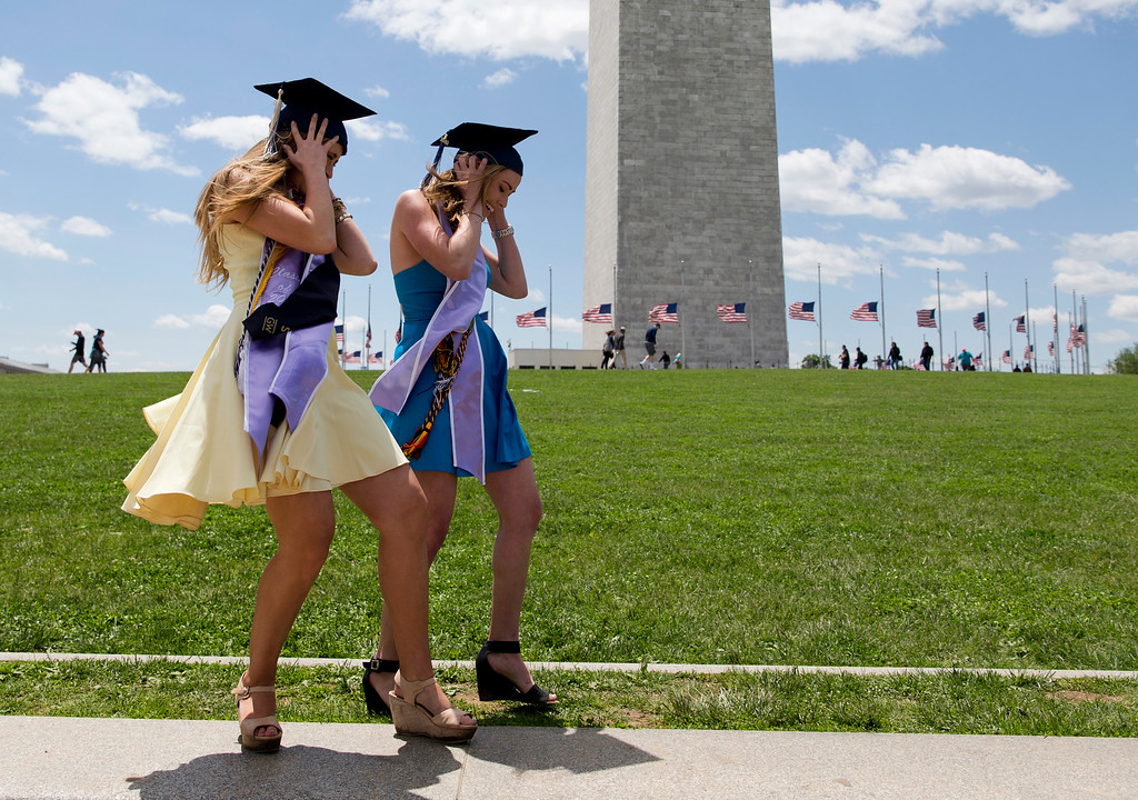 . George Washington University graduates Serena Williams, left, and Hannah Raymond, right, struggle against a strong wind as they pose for graduations pictures near the Washington Monument, Sunday, May 15, 2016, in Washington, after their commencement ceremony on the National Mall. (AP Photo/Carolyn Kaster)