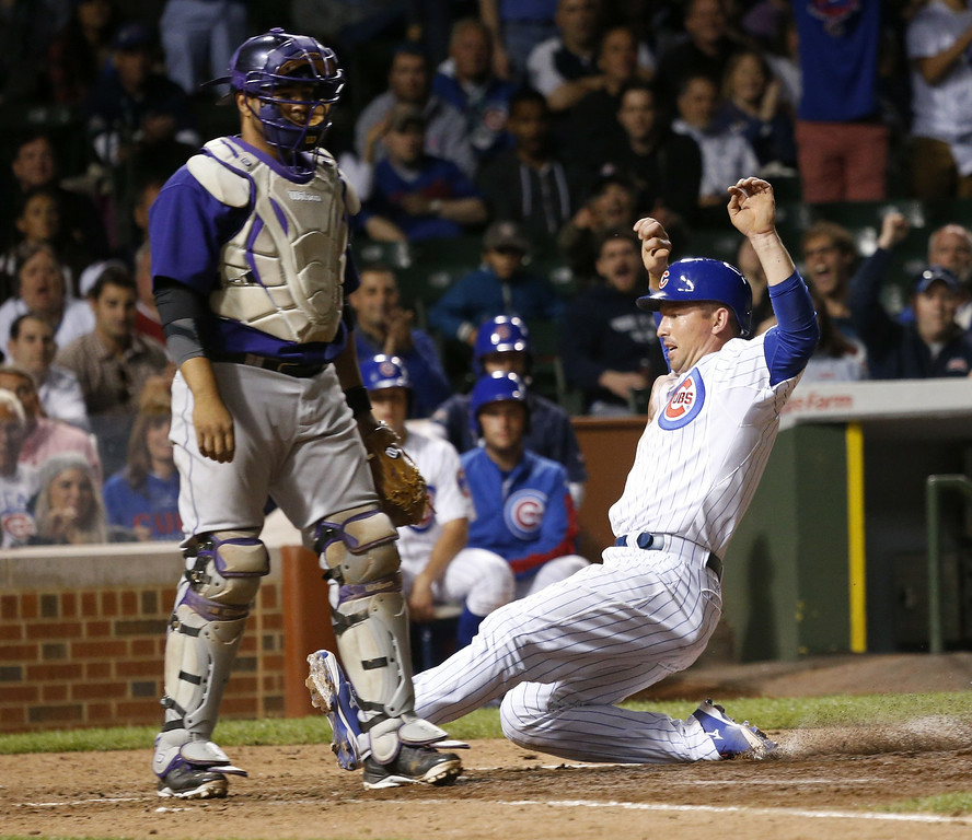 . Chicago Cubs\' John Baker, right, scores past Colorado Rockies catcher Wilin Rosario after pitcher Nick Masset made a throwing error on a pick off attempt at first during the eighth inning of a baseball game Monday, July 28, 2014, in Chicago. The Cubs won 4-1. (AP Photo/Charles Rex Arbogast)
