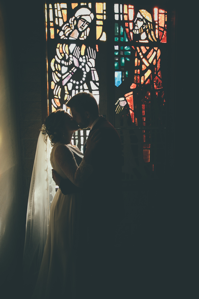 A bride and groom kissing in front of a stained glass wind of o their church in which they have just wed