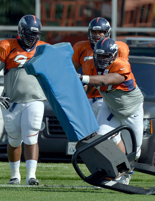 . Denver Broncos DT Sylvester Williams (92) hits the sled during training camp August 6, 2013 at Dove Valley. (Photo By John Leyba/The Denver Post)