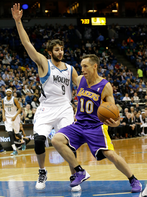 . Los Angeles Lakers guard Steve Nash (10) drives against Minnesota Timberwolves guard Ricky Rubio (9), of Spain, during the first quarter of an NBA basketball game in Minneapolis, Friday, March 28, 2014.  (AP Photo/Ann Heisenfelt)
