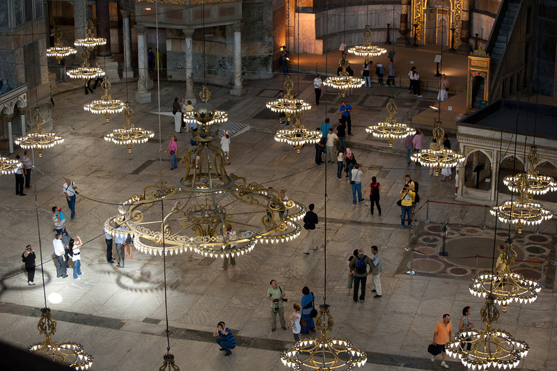 Beautiful chandelier hanging above tourists in Hagia Sophia - Istanbul, Turkey