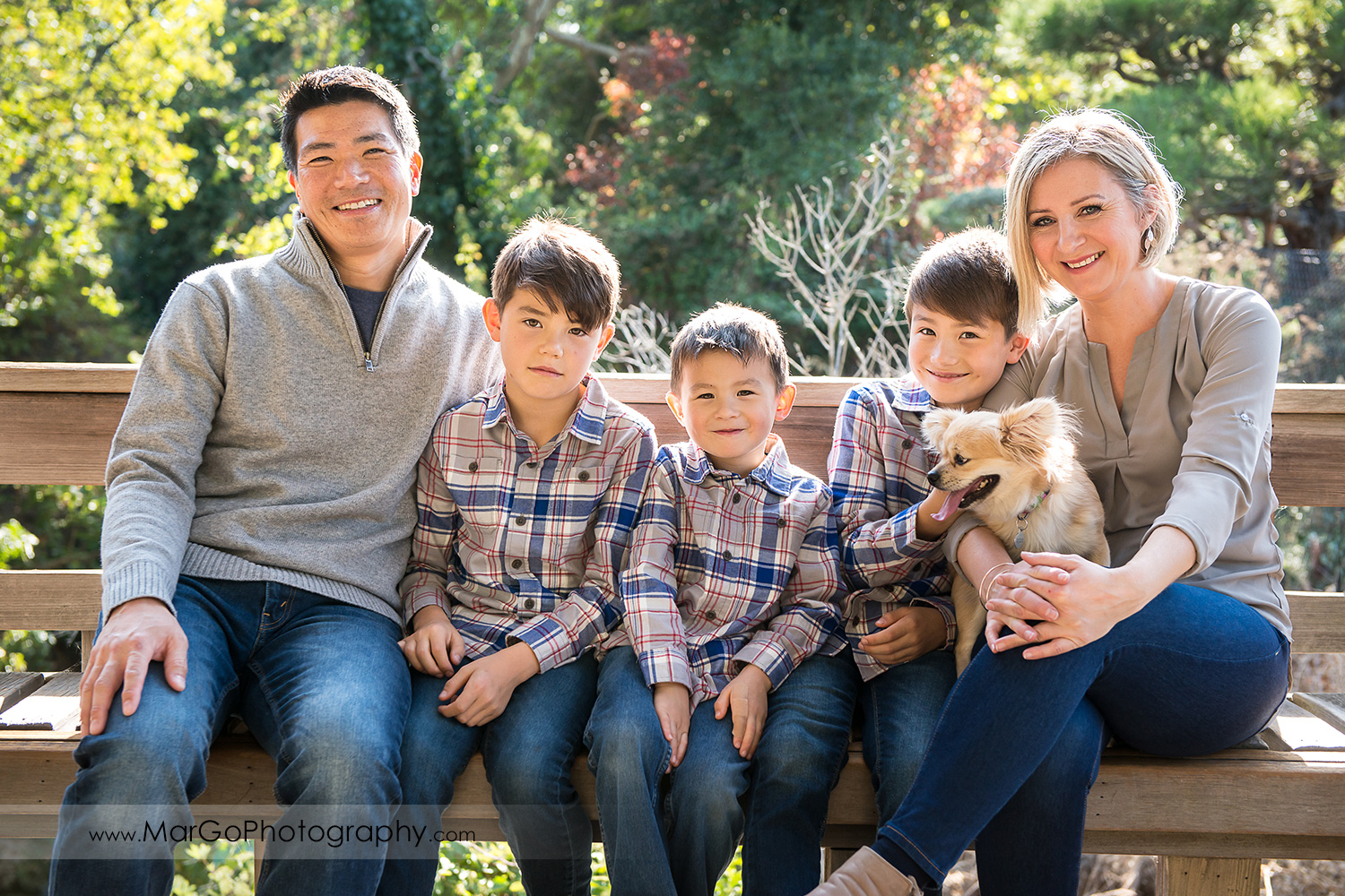 portrait of family of five in gray shirts and a dog looking into camera sitting on the wood bench with a dog at Hayward Japanese Garden