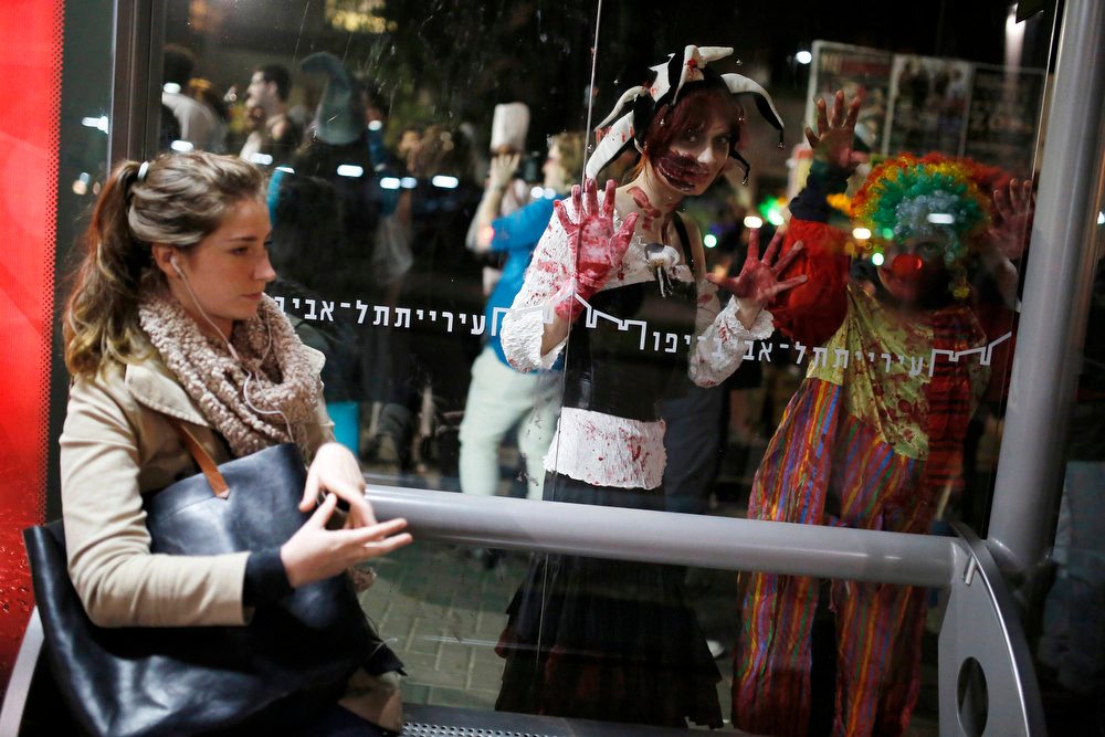 Description of . Israelis dressed as zombies look through a window at a bus station as they take part in an annual Zombie Walk procession for the Jewish holiday of Purim in Tel Aviv February 23, 2013. Purim is a celebration of the Jews\' salvation from genocide in ancient Persia, as recounted in the Book of Esther. Picture taken February 23, 2013. REUTERS/Amir Cohen