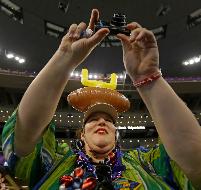 . NFL football fan Karen Vine Fuller of Houston wearing a goalpost hat shoots photos of the San Francisco 49ers during media day for the NFL Super Bowl XLVII football game Tuesday, Jan. 29, 2013, in New Orleans. (AP Photo/Gerald Herbert)