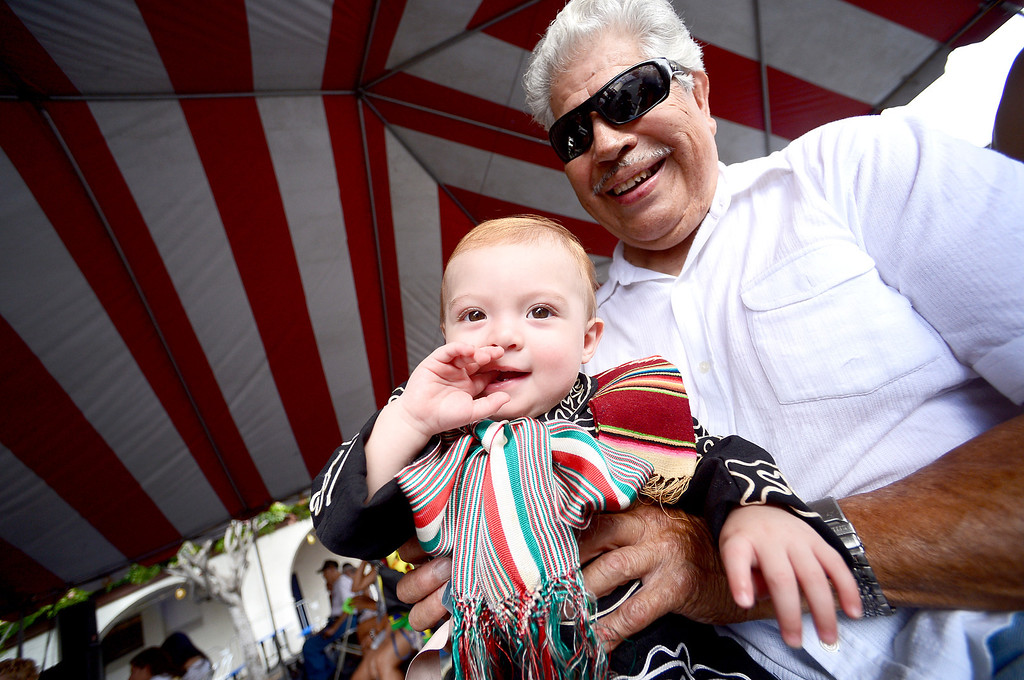 . Landon Herrera, 11 months, of San Gabriel, is about to compete in a children\'s costume contest as he sits with his 88-year-old great-grandfather Manuel during the 242nd Annual La Fiesta de San Gabriel Saturday, August 31, 2013 at the San Gabriel Mission. Landon was the third generation in the Herrera family to wear the Charro costume. Jorge Ruiz, 8, of San Gabriel, is wearing a Oaxacan outfit. The fiesta runs through Sunday. (Photo by Sarah Reingewirtz/Pasadena Star-News)