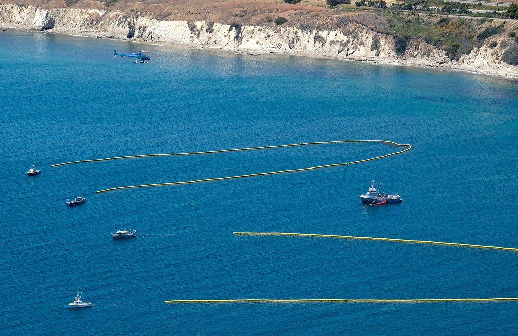 . A helicopter coordinates ships below pulling booms to collect oil from a spill near Refugio State Beach, north of Goleta, Calif., Wednesday, May 20, 2015. A broken onshore pipeline spewed oil down a storm drain and into the ocean for several hours Tuesday before it was shut off. (AP Photo/Michael A. Mariant)