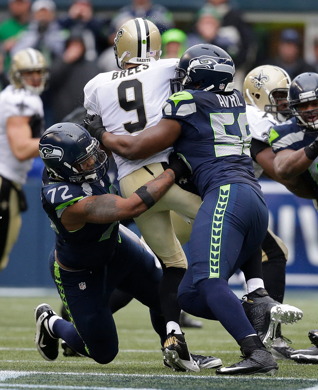 . Seattle Seahawks defensive end Michael Bennett (72) and defensive end Cliff Avril (56) sack New Orleans Saints quarterback Drew Brees (9) during the third quarter of an NFC divisional playoff NFL football game in Seattle, Saturday, Jan. 11, 2014. (AP Photo/Elaine Thompson)