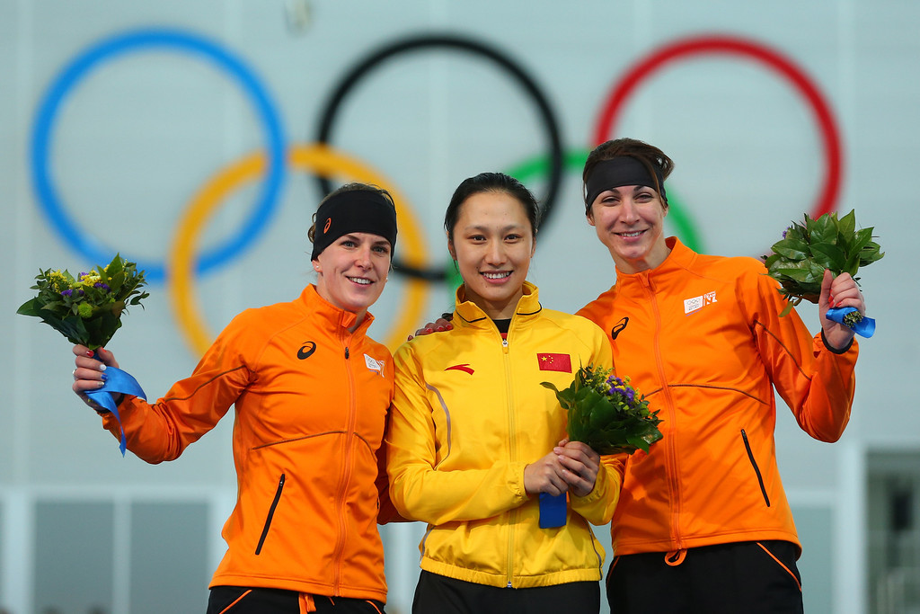 . (L-R) Silver medalist Ireen Wust of the Netherlands, gold medalist Hong Zhang of China and bronze medalist Margot Boer of the Netherlands celebrate on the podium during the flower ceremony for the Speed Skating Women\'s 1000m event on day 6 of the Sochi 2014 Winter Olympics at Adler Arena Skating Center on February 13, 2014 in Sochi, Russia.  (Photo by Quinn Rooney/Getty Images)