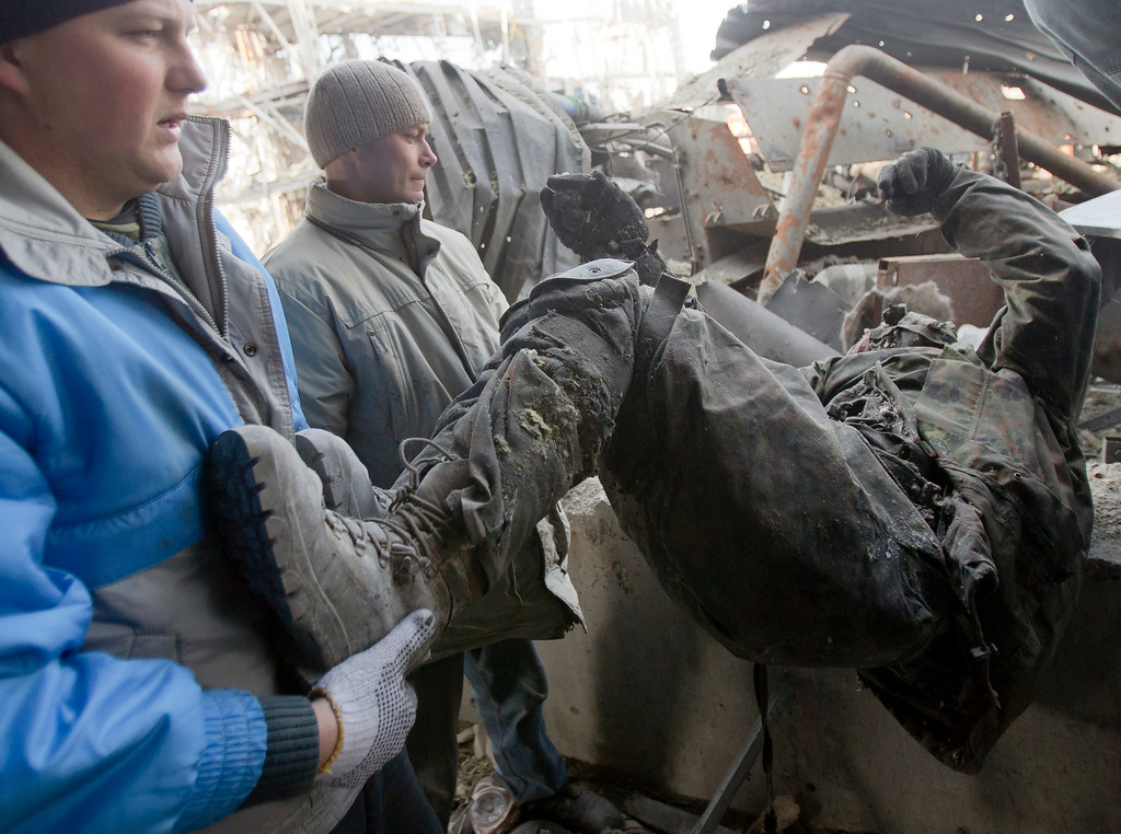 . Ukrainian prisoners of war remove the body of a Ukrainian serviceman from the rubble of the airport building outside Donetsk, Ukraine, Wednesday, Feb. 25, 2015. Ukrainian troops held captive in the separatist stronghold of Donetsk began digging through the rubble Wednesday to retrieve the bodies of fellow soldiers killed last month in a bitter battle for the city\'s airport. (AP Photo/Vadim Ghirda)