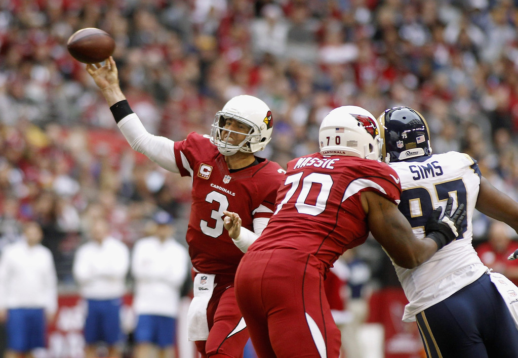 . Quarterback Carson Palmer #3 of the Arizona Cardinals throws a pass as Cardinals\' lineman Bobby Massie #70 blocks Eugene Sims #97 of the St Louis Rams during the second quarter of their NFL football game at University of Phoenix Stadium on December 8, 2013 in Glendale, Arizona.  (Photo by Ralph Freso/Getty Images)