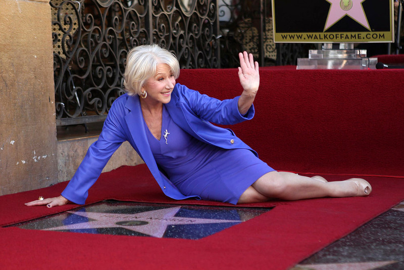 ". Helen Mirren waves as she poses with her newly-unveiled star, the 2,488th star on the Hollywood Walk of Fame, in Hollywood, California, January 3, 2013. The multi major award-winning actress was recently nominated for a Golden Globe Award by the Hollywood Foreign Press Association for Best Actress in a Motion Picture: Drama and for a Screen Actors Guild Award for Best Actress in a Motion Picture Drama. Mirren will appear in the HBO biopic ""Phil Spector\"" later this year.   REUTERS/David McNew ("