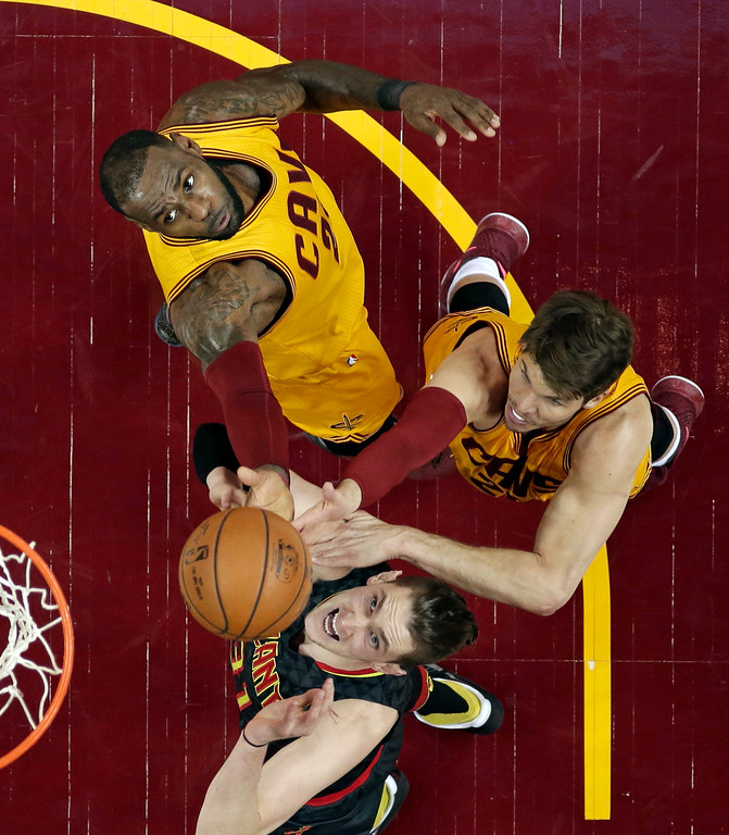 . Atlanta Hawks\' Mike Muscala, bottom, drives to the basket against Cleveland Cavaliers\' LeBron James, top, and Kyle Korver, right, in the first half of an NBA basketball game, Friday, April 7, 2017, in Cleveland. (AP Photo/Tony Dejak)