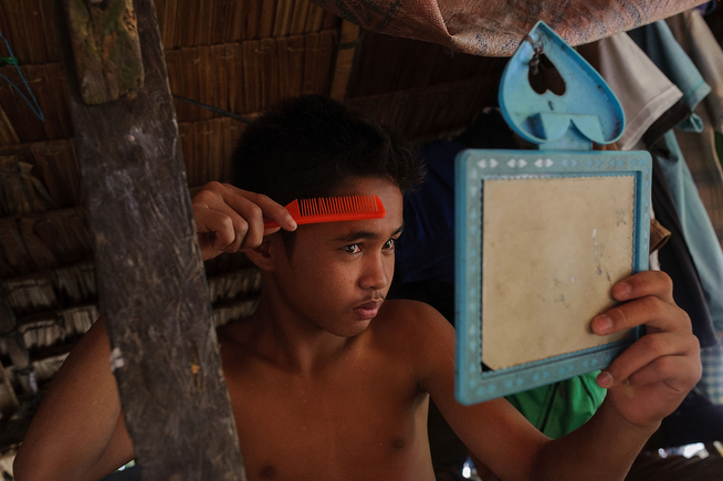 . A 14-year-old gold miner styles his hair at the end of a day of mining, on April 23, 2014 in Pinut-An, Philippines. (Photo by Luc Forsyth/Getty Images)