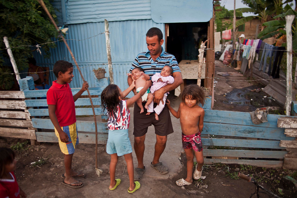 ". In this April 8, 2013 photo, Eduardo Gonzalez, 30, holds his babies outside his aluminum shack in a squatter\'s settlement near Tacarigua, Venezuela. Outside Venezuela\'s capital, power outages, food shortages and unfinished projects abound; important factors heading into Sunday\'s election to replace Venezuela\'s late President Hugo Chavez, who died last month after a long battle with cancer. An estimated 2 million of Venezuela\'s country\'s nearly 30 million people lack permanent homes, and one of Chavez\'s anti-poverty ""missions\"" builds them. But it\'s been slow going. The government says it has built 370,500 homes and apartments over the past two years, and more than 3 million people applied for them. (AP Photo/Ramon Espinosa)"