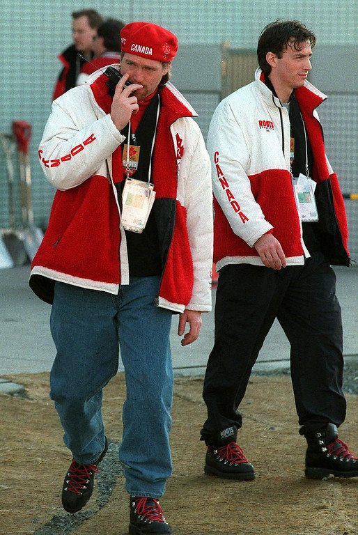 . Canadian Olympic Hockey team goaltender Patrick Roy, left, talks on a phone as he and forward Joe Sakic, right, leave the \'Big Hat\' Olympic hockey rink in Nagano, Japan Thursday Feb. 19, 1998. (AP PHOTO/Fred Chartrand)