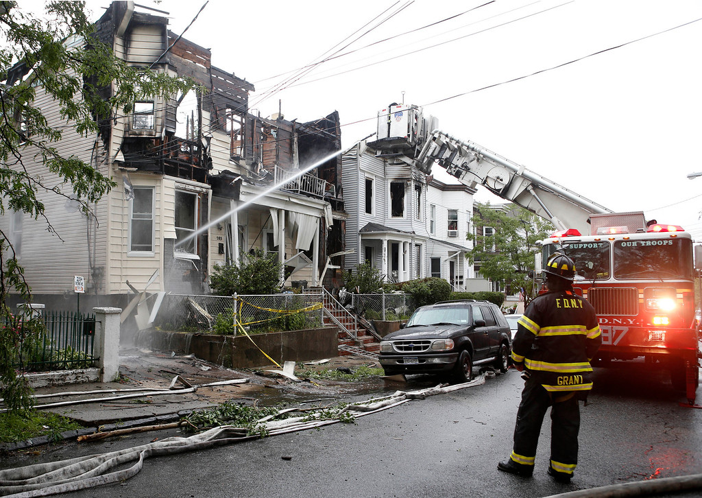 . A firefighter, right, watches as another sprays water on 205 Chestnut Avenue in the Staten Island borough of New York, Thursday, June 5, 2014, where 34 people were injured after fire tore through three townhouses on the street early Thursday. (AP Photo/Kathy Willens)