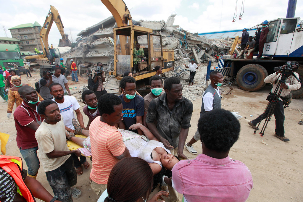 . Rescue workers carry a survivor from the rubble of a collapsed building belonging to the Synagogue Church of All Nations in Lagos, Nigeria, Saturday, Sept, 13. 2014. The building was being extended, adding 2 additional floors when it collapsed. (AP Photo/Sunday Alamba)