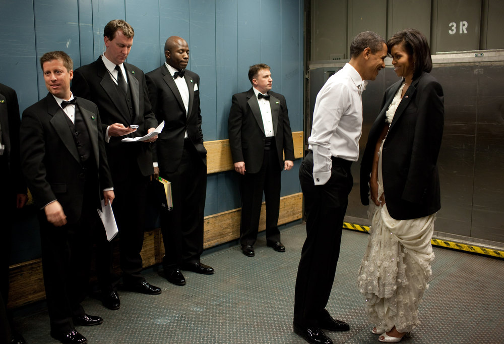 "Description of . Jan. 20, 2009 ""We were on a freight elevator headed to one of the Inaugural Balls. It was quite chilly, so the President removed his tuxedo jacket and put it over the shoulders of his wife. Then they had a semi-private moment as staff member and Secret Service agents tried not to look.""  (Official White House photo by Pete Souza)"