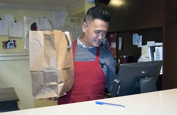 03/27/20 Wesley Bunnell | Staff Frank Kwok , co owner of Great Taste Restaurant, holds a to go bag as he rings out a customer at his restaurant on Monday afternoon. Governor Ned Lamont ordered all restaurants closed effective at 8 p.m. with the exception of take out and delivery.